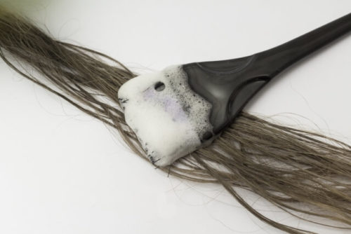 マイナチュレをハケで髪に塗っている様子